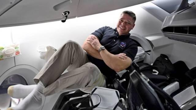 El astronauta Bob Behnken posa al interior de la nave Dragon de la compañía SpaceX, que podría convertirse este domingo en la primera en enviar y traer astronautas del espacio
