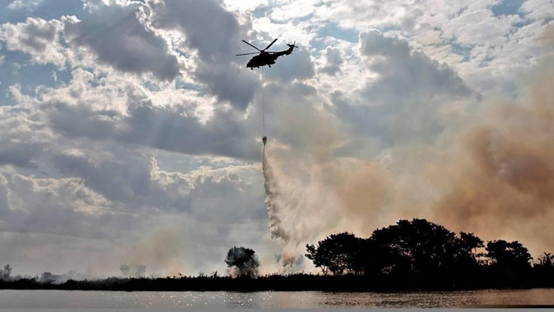 Un helicóptero realiza labores de lucha contra incendios, cerca de la ciudad de Corumbá donde se encuentra el pantanal brasileño de Mato Grosso, uno de los mayores humedales del planeta