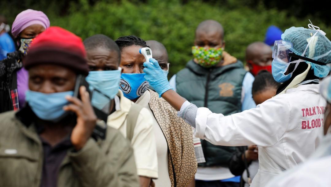 Personas en fila en África, mientras les toman la temperatura