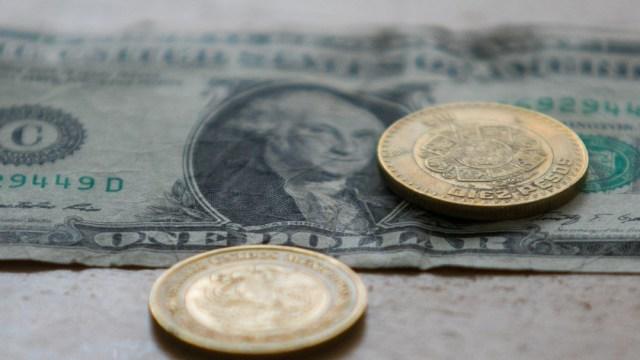 Fotografía que muestra un dólar y dos monedas de 10 pesos mexicanos