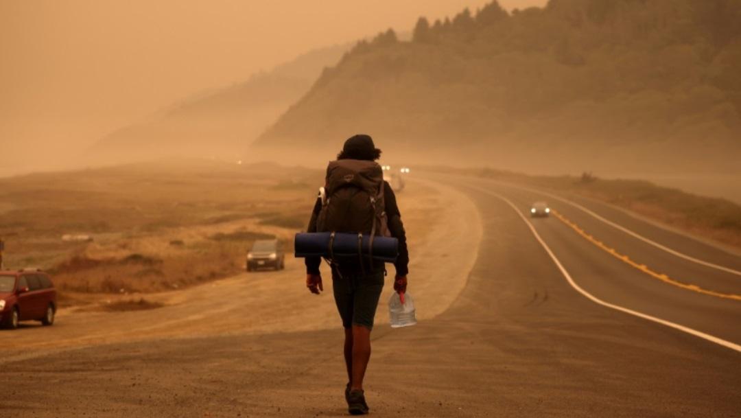 Un hombre camina entre una densa de humo en California