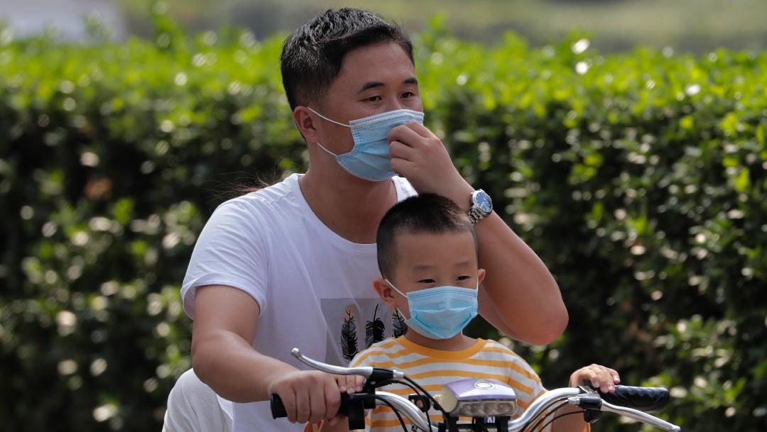 Hombre y niño con cubrebocas en bicicleta en China