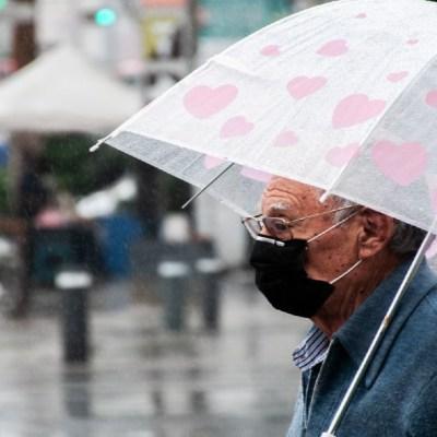 Un hombre de la tercera edad se cubre con un paragüas de la lluvia