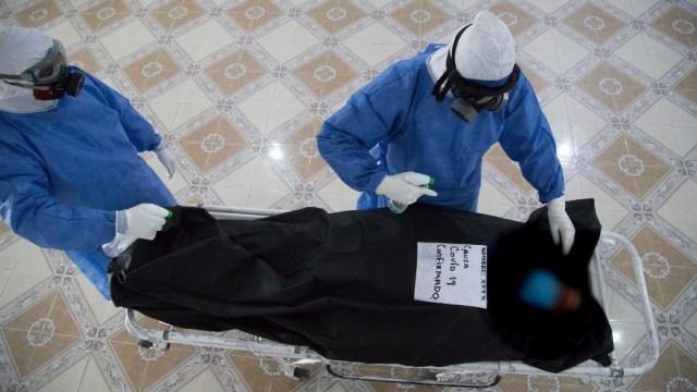 Empleados de una funeraria manipulan un cuerpo tras ser declarado muerto Covid-19. (Foto: Cuartoscuro)
