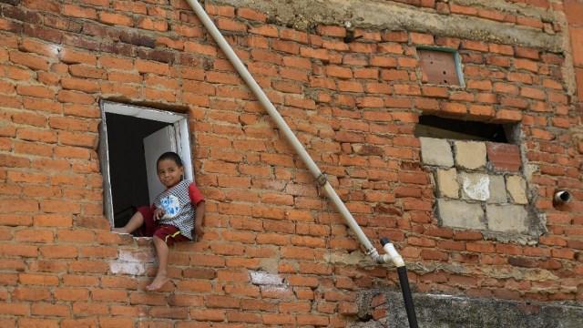 Niño sentado en ventana de edificio