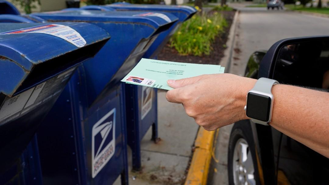 Persona colocando un documento en buzón de correo en Estados Unidos