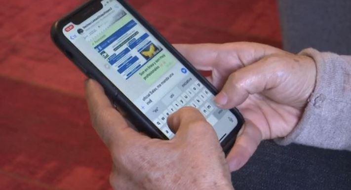 Persona usando un celular para mandar mensaje de WhatsApp a la Policía