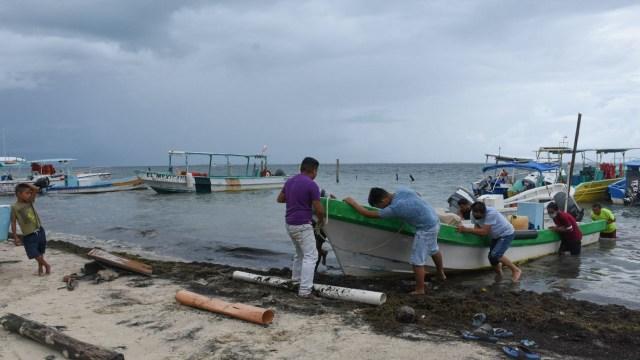 Pescadores en Cancún empiezan a resguardar sus embarcaciones debido a que se esperan lluvias intensas para este fin de semana