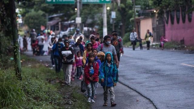 Migrantes hondureños continúan su camino en caravana hacia EEUU mientras caminan por una carretera de Guatemala