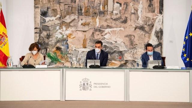 El presidente del Gobierno, Pedro Sánchez (c), acompañado por la vicepresidenta Primera, Carmen Calvo (i), y el vicepresidente segundo, Pablo Iglesias