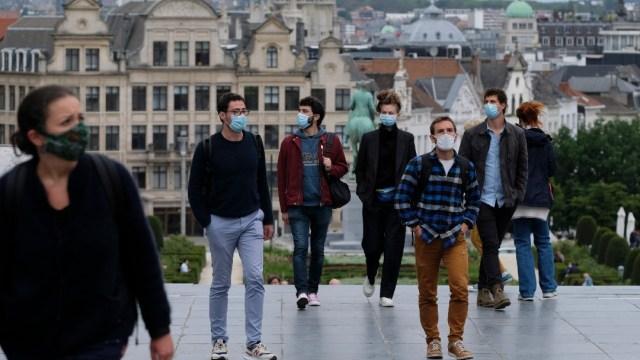 Varias personas con mascarilla pasan por la Grand Place de Bruselas