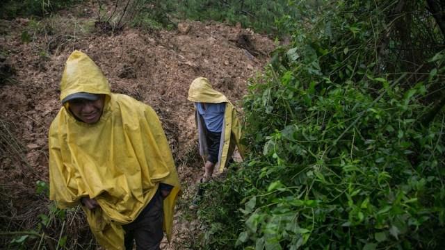 Pobladores cruzan a través de caminos improvisados por los derrumbes ocasionados por el huracan Eta