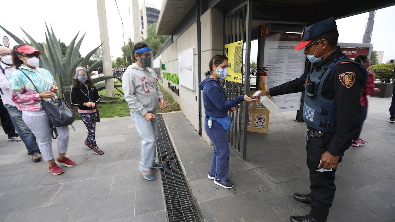 Ciudadanos reciben gel antibacterial antes de ingresar a los centros de votación