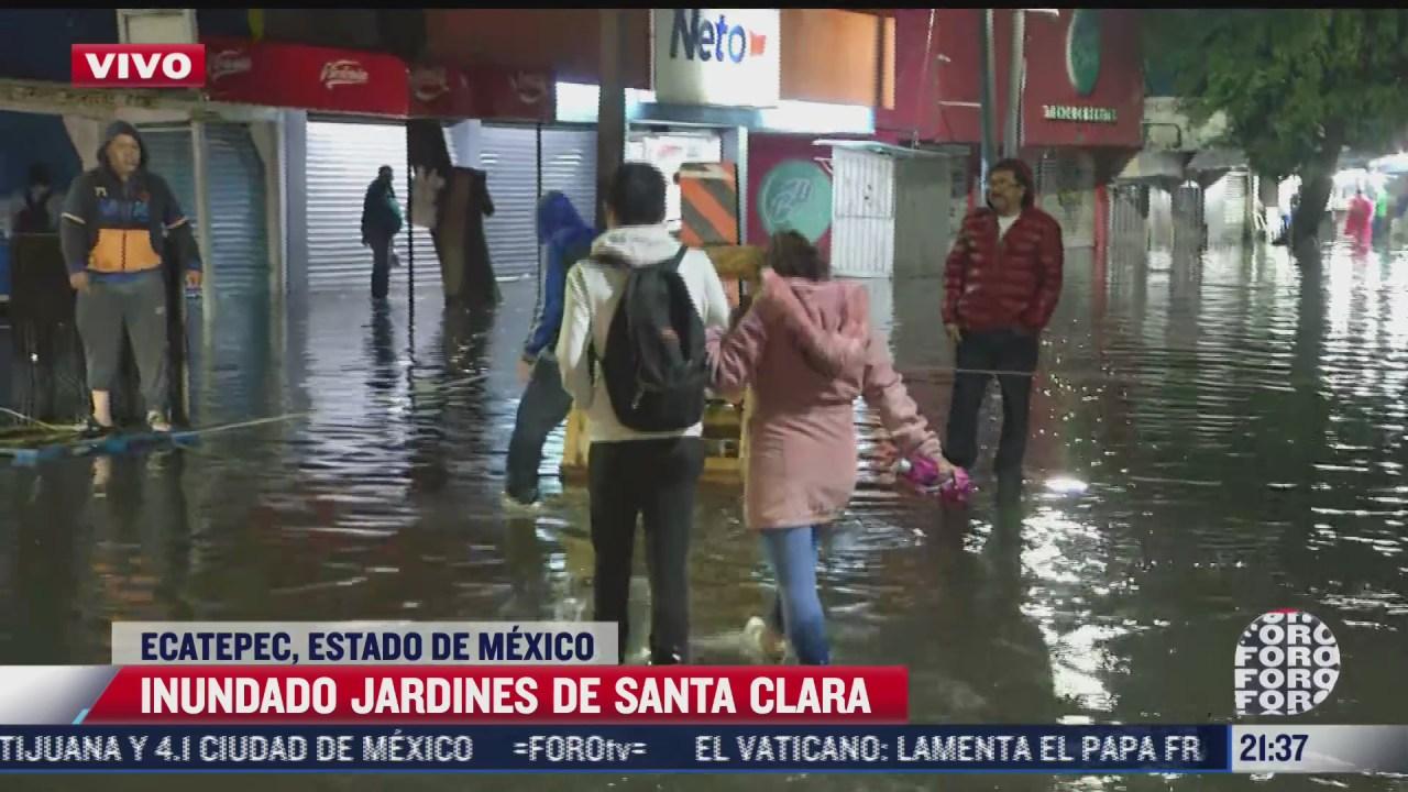 pobladores de ecatepec caminan por calles inundadas para llegar a sus domicilios