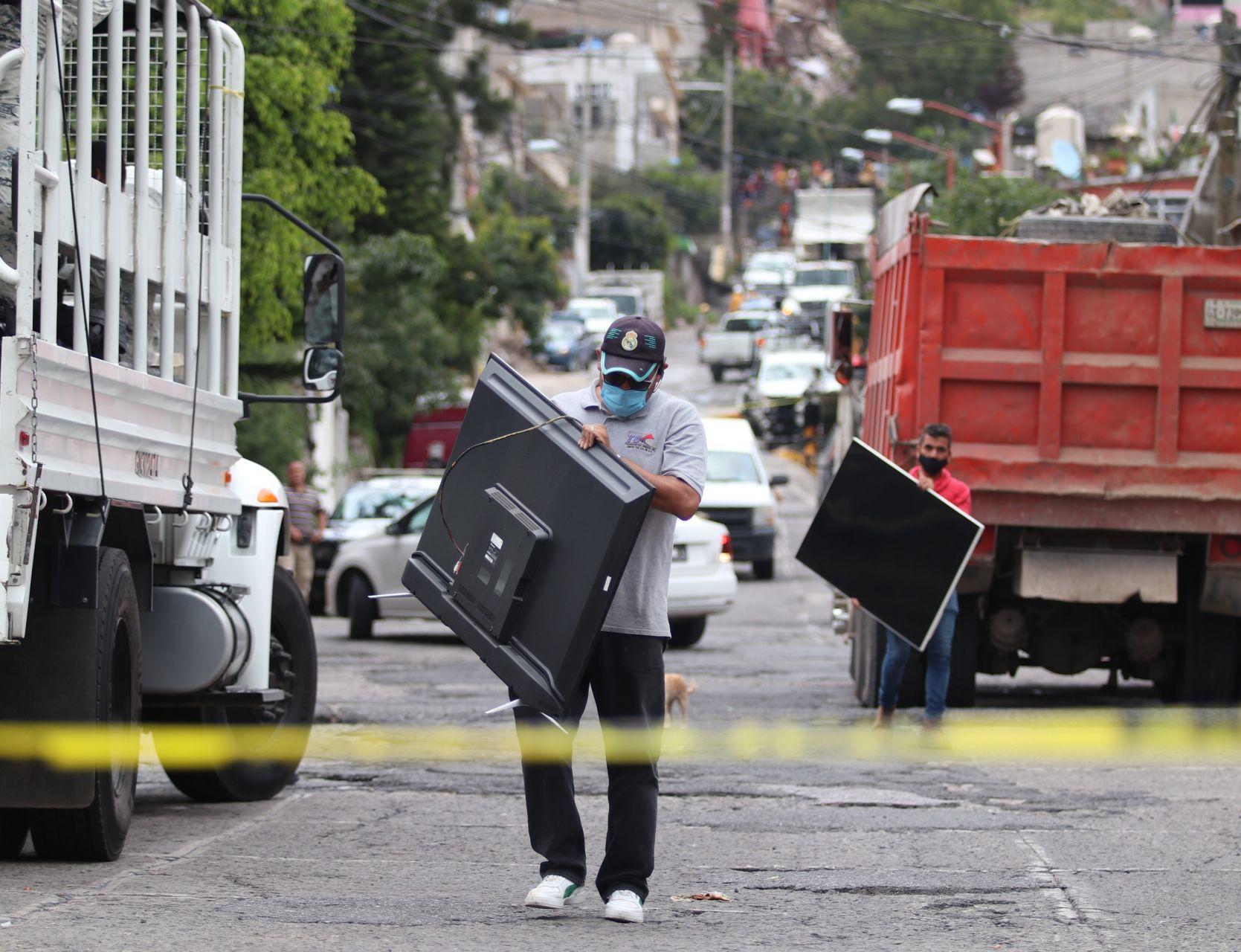 Habitantes de las casas desalojadas sacan algunas pertenencias