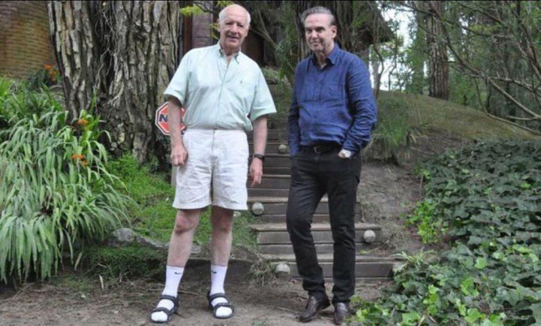 Roberto Lavagna usando sandalias con medias blancas junto a Miguel Ángel Pichetto