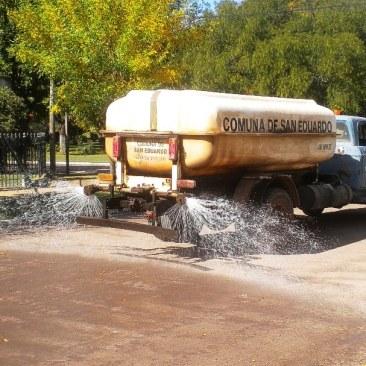 Y pasa el camión, regando las calles; el chorro alcanza justito hasta el borde
