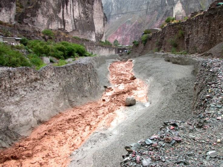 El agua marrón baja con fuerza. El color distingue abruptamente del resto de la montaña