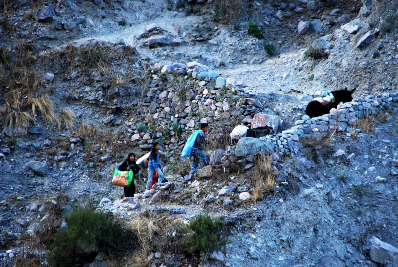 Cargando bolsas, subiendo la escalera en zigzag. El burro también lleva una carga. (Foto: Andrea Semplici).
