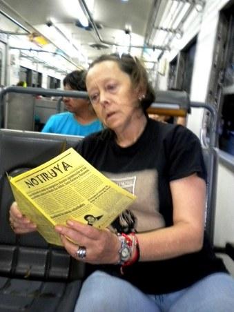 Ana, concentrada en la lectura de NOTIRUYA, en el tren en Buenos Aires