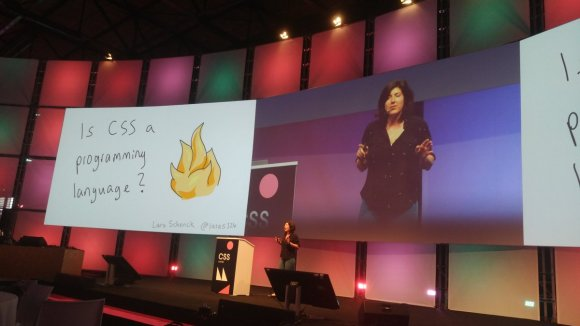"Lara giving a talk on a big stage, with a slide that says ""Is CSS a programming language?"""