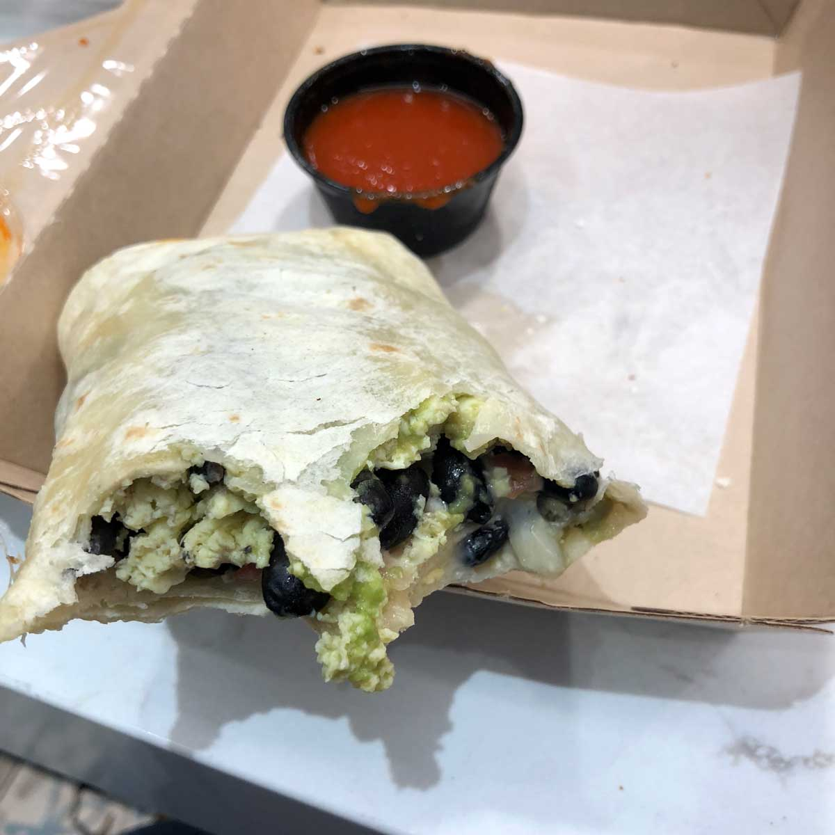 A partially eaten burrito in a to-go container