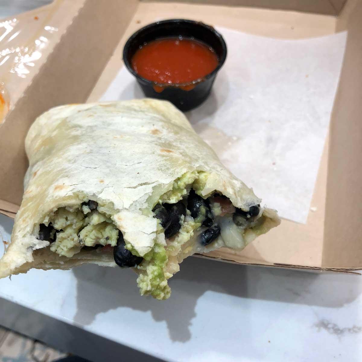 A partially eaten burrito in a to-go container