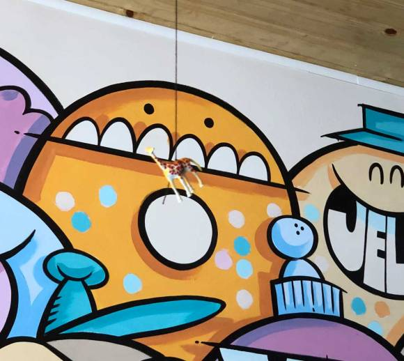A small toy giraffe hanging from the ceiling in front of  a colorful mural