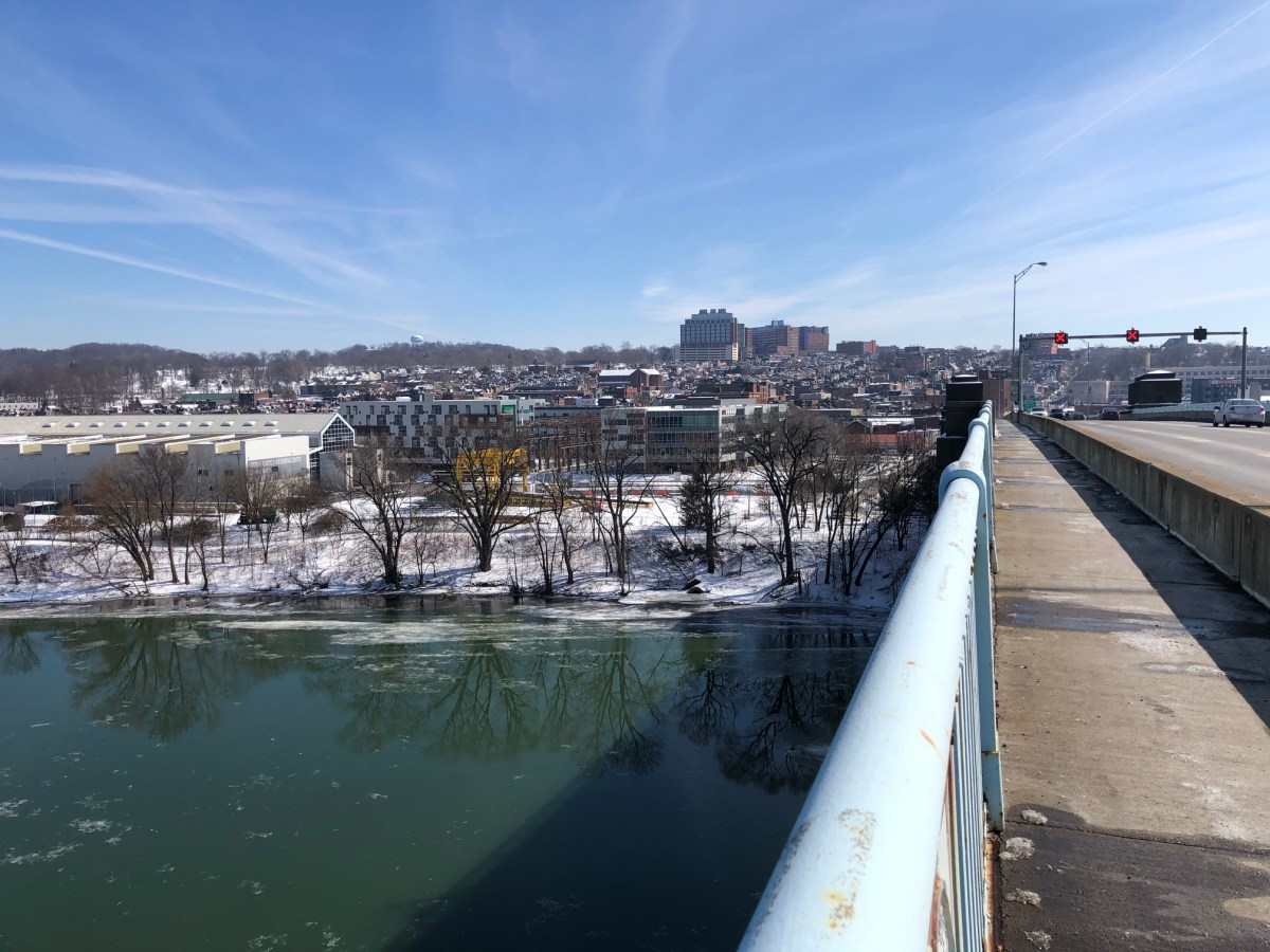 A photo of a clear sky from a bridge over the river and a town