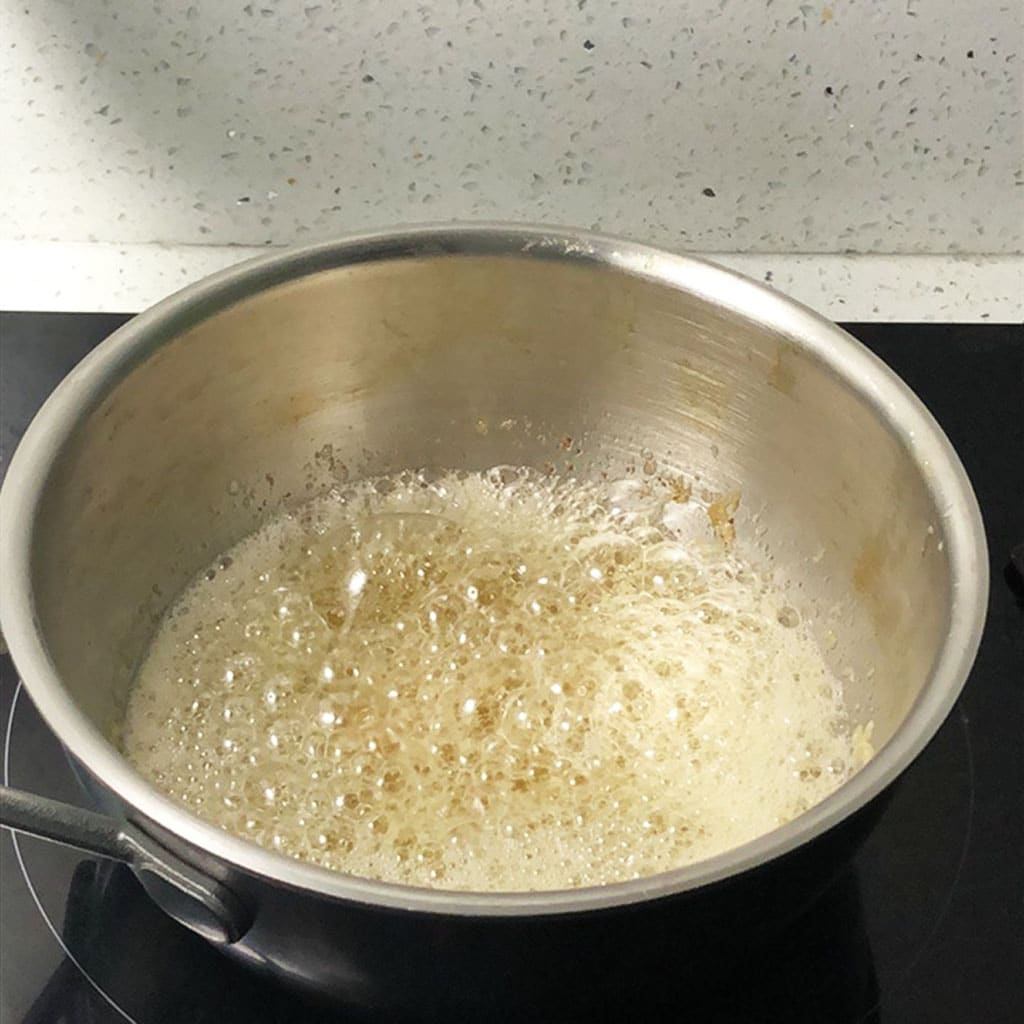 Boiling butter is foaming in a saucepan.