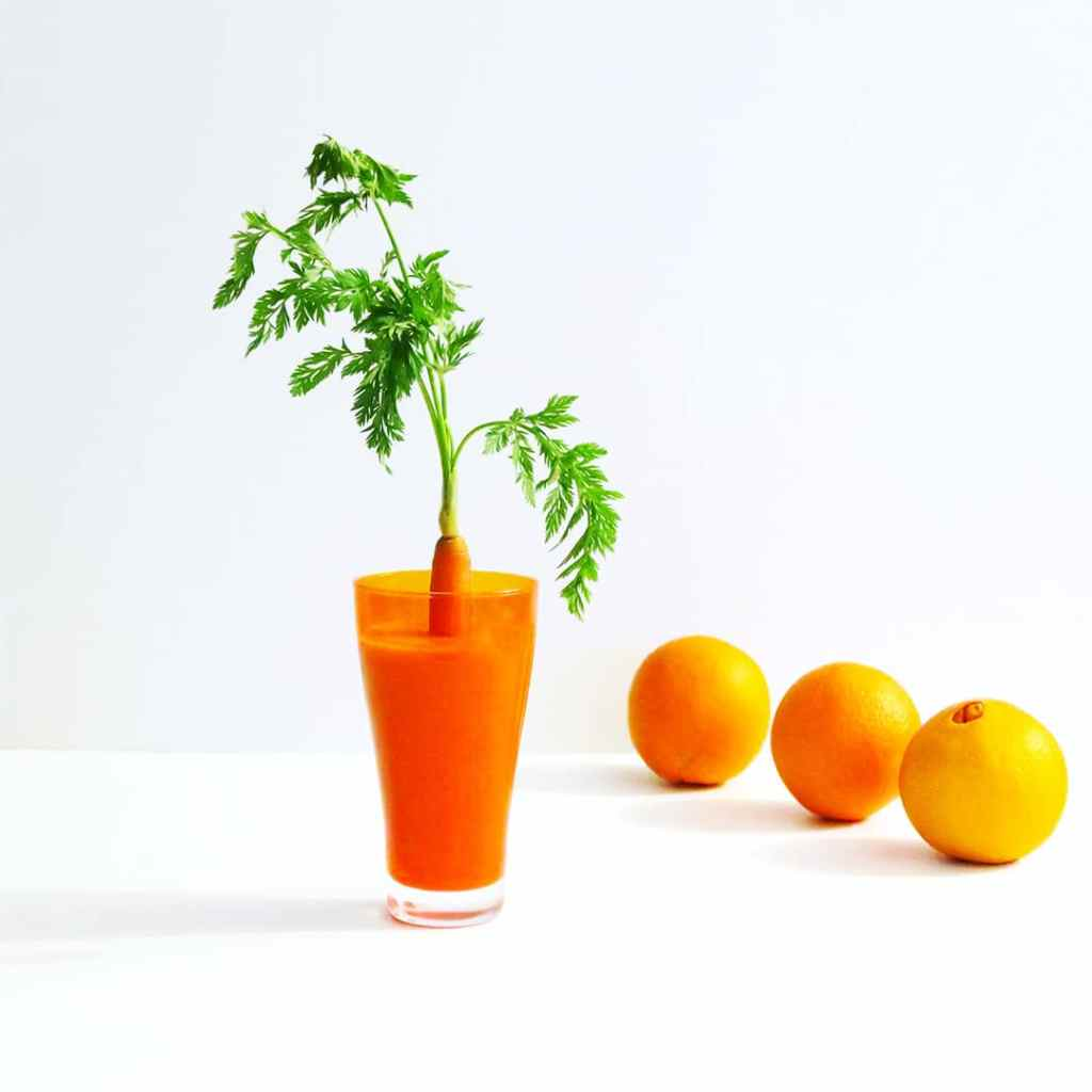 Carrot Smoothie in a orange glass, with a carrot top sticking out of it and three oranges in the background on a white surface