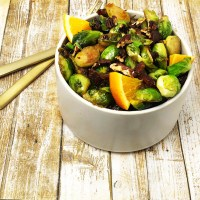 Cream coloured bowl filled with pan-fried brussell sprouts with orange, dates, and pecans