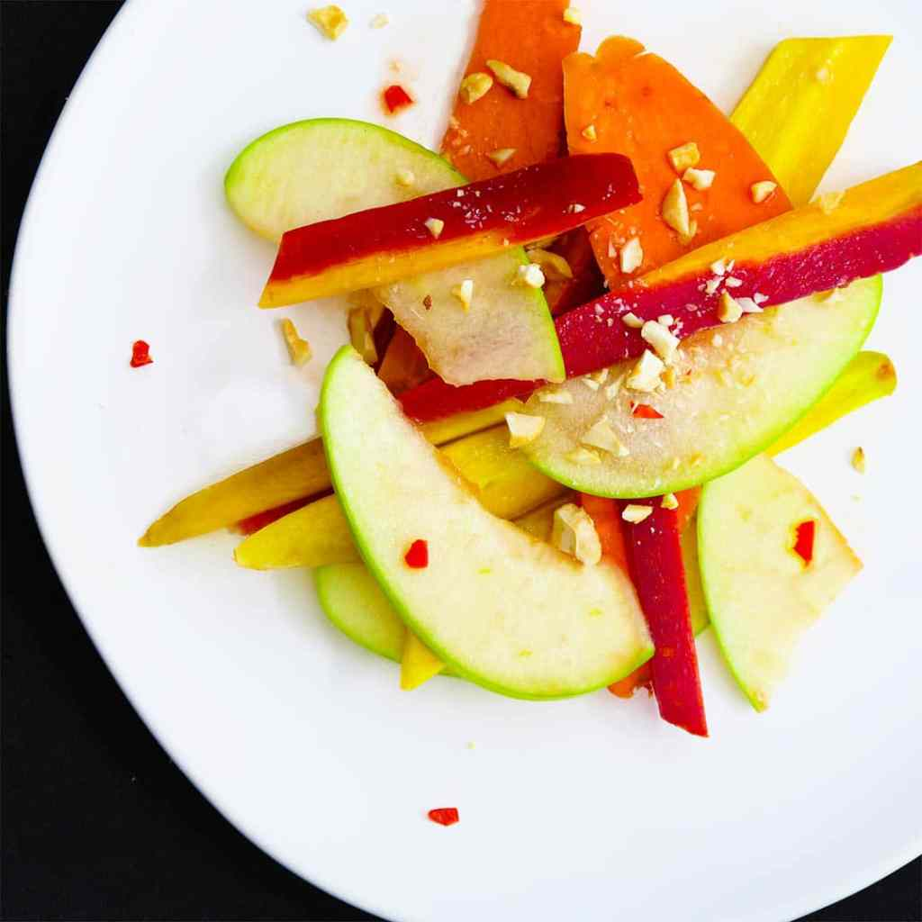 Thai Apple Salad on a white plate on a black background