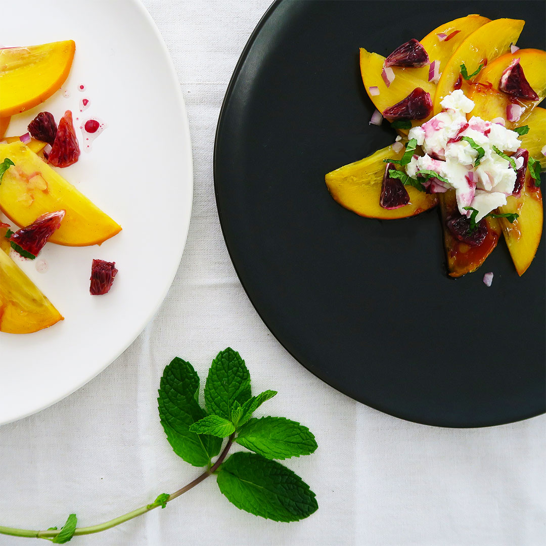 Blood Orange Breakfast Salad recipe. Black plate shows vegan version with salted cream cheeze.