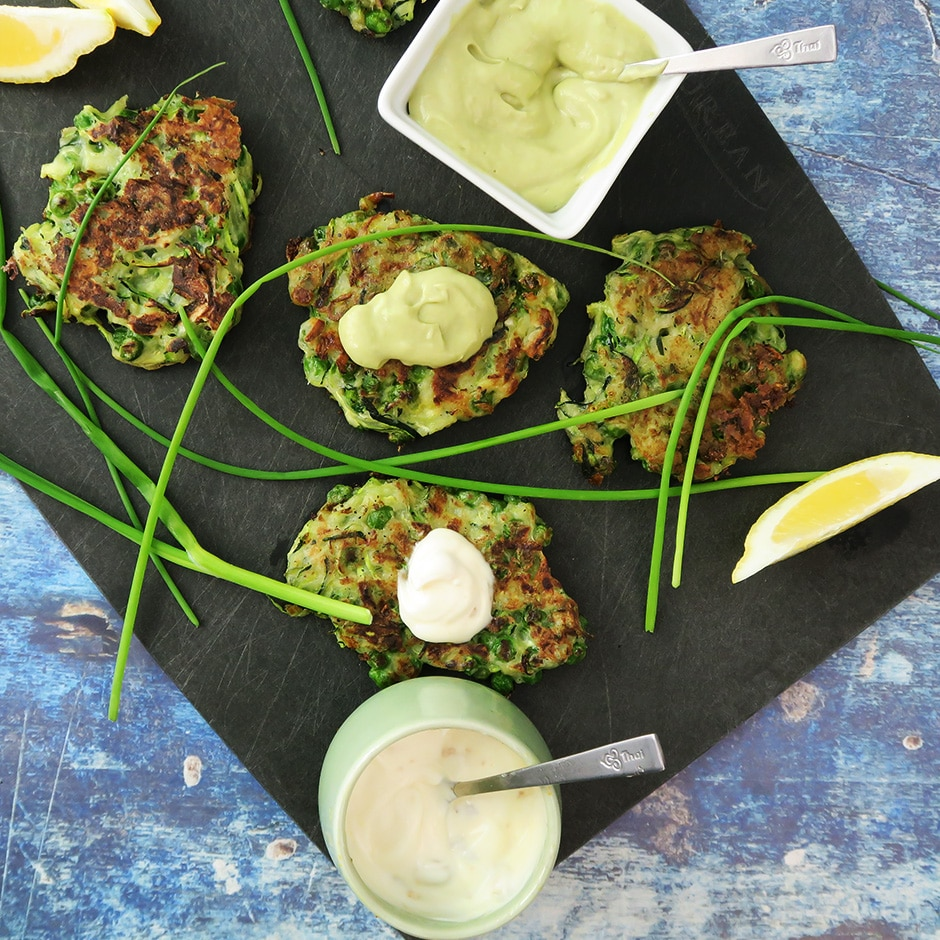 Top down view of Zucchini and Green Pea Fritters with Avocado Crema, on a black serving board, and garnished with chives and lemon