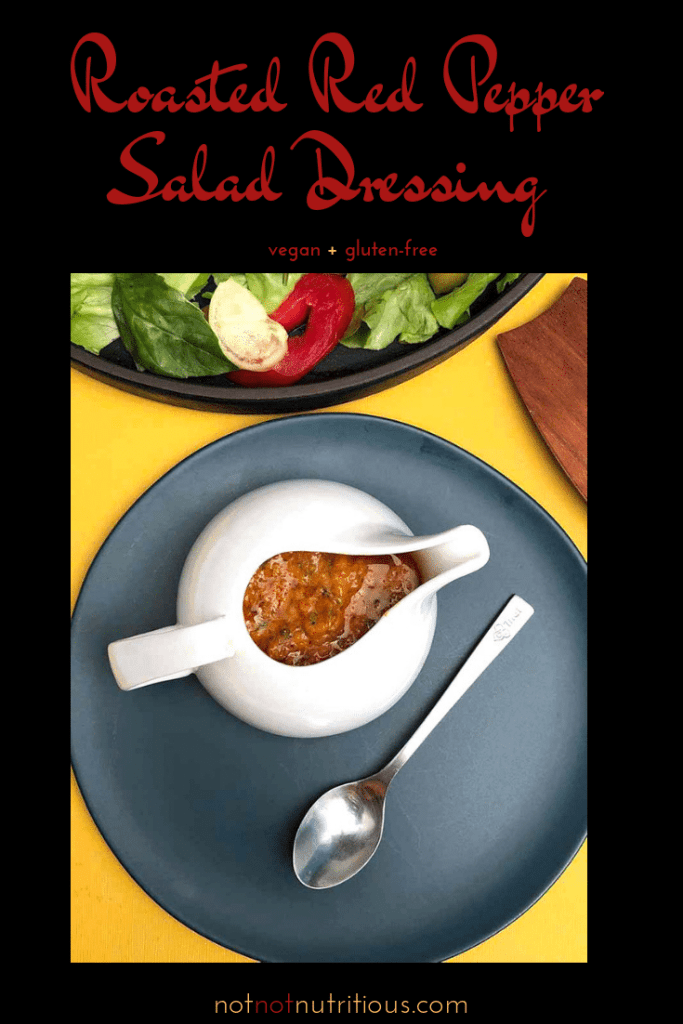 Roasted Red Pepper Salad Dressing in a white serving vessel on a blue plate with a spoon