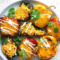 A colourful array of stuffed peppers, green, yellow, and red, topped with cheese, sour cream, and cilantro. From the recipe: Mexican Stuffed Pepper Three Ways - Vegan, Vegetarian, Omnivore