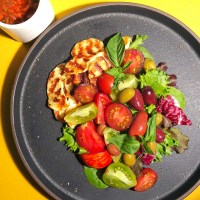 Mediterranean Salad, an entree salad with either chicken or Halloumi, tomatoes, olives, fresh basil, and vibrant greens, on a black plate
