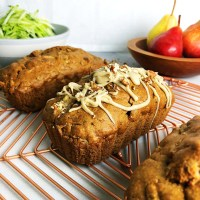 Three loaves of Pear and Zucchini Bread on a copper-coloured cooling rack, with a bowl of pears, and another bowl of shredded zucchini in the background.