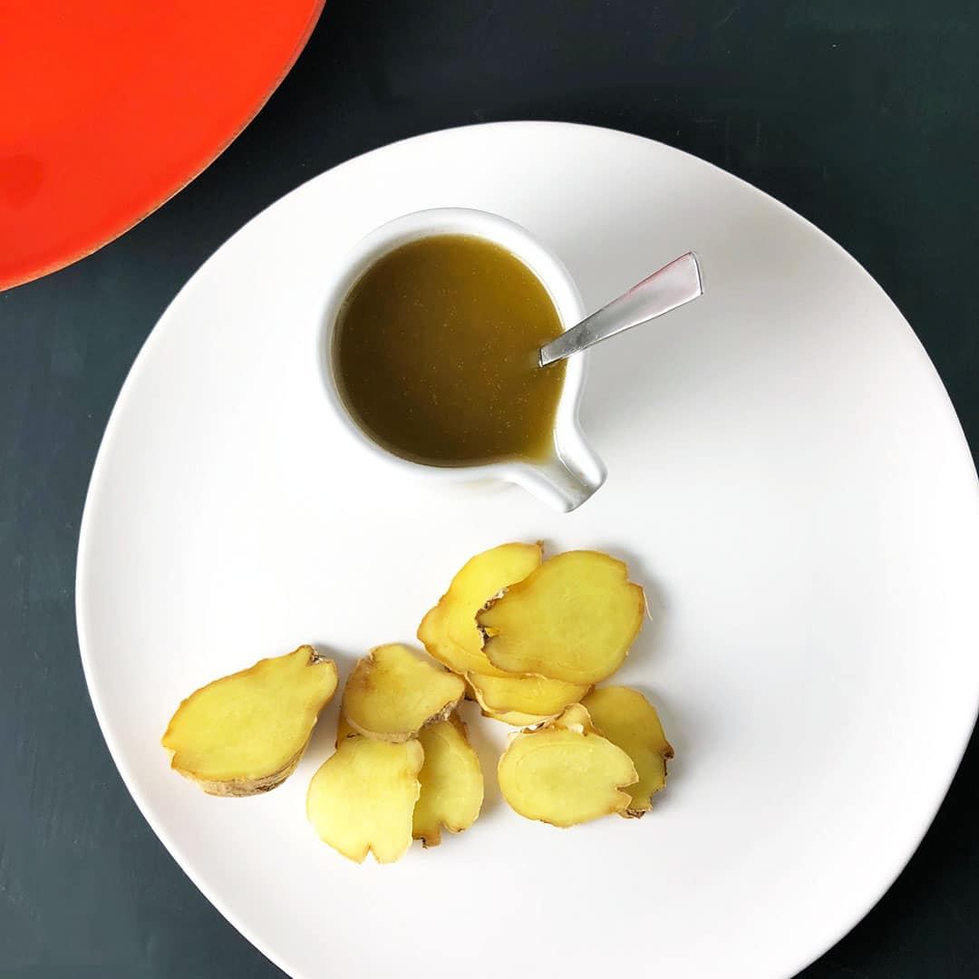 Top down shot of small white pitcher with ginger brown butter sauce, with pieces of fresh ginger on a white plate.