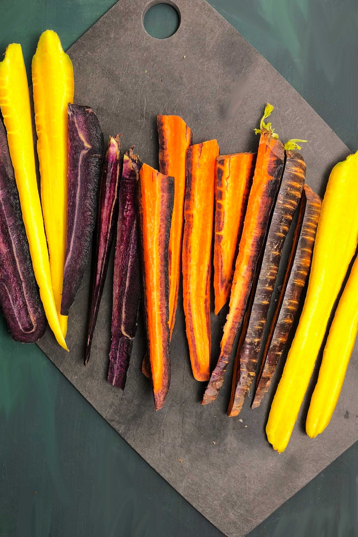 Sliced rainbow carrots on a cutting board. Carrots are yellow, orange, and purple.