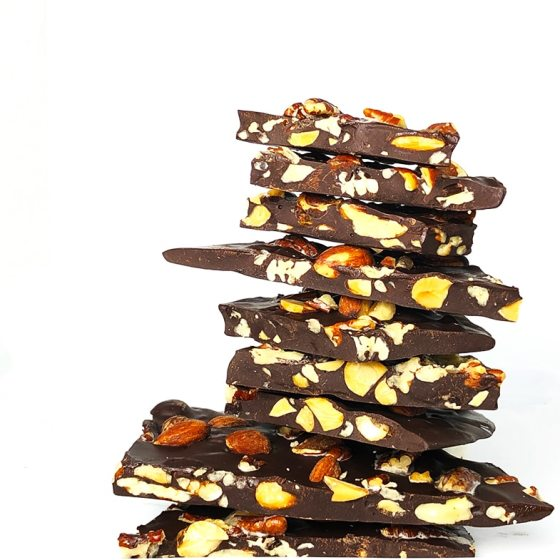 A towering pile of dark chocolate bark studded with pecans and almonds against a white background.
