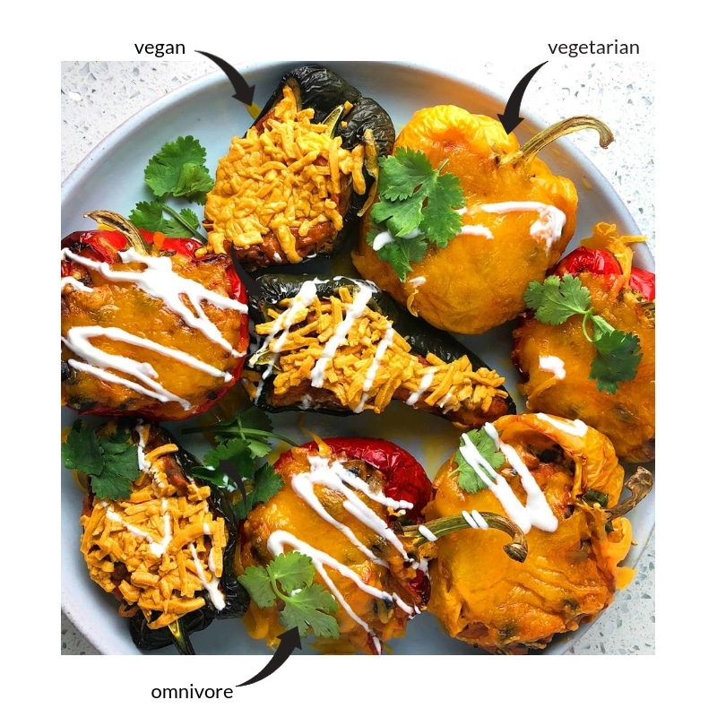 Topdown view of Mexican Stuffed Peppers, green peppers with vegan cheese, orange peppers are vegetarian, and red peppers have meat.
