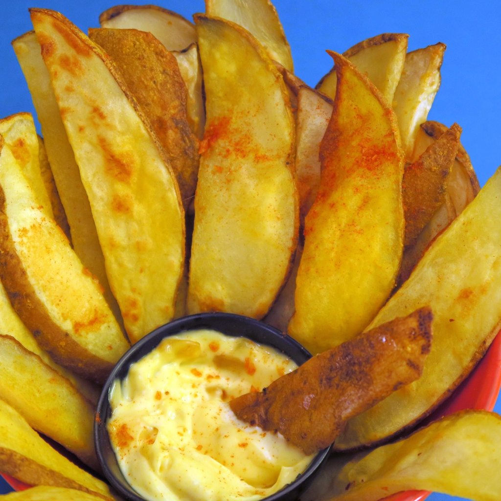 Cheesy Battered Oven fries in a bowl, with a fry dipped in garlic mayo.