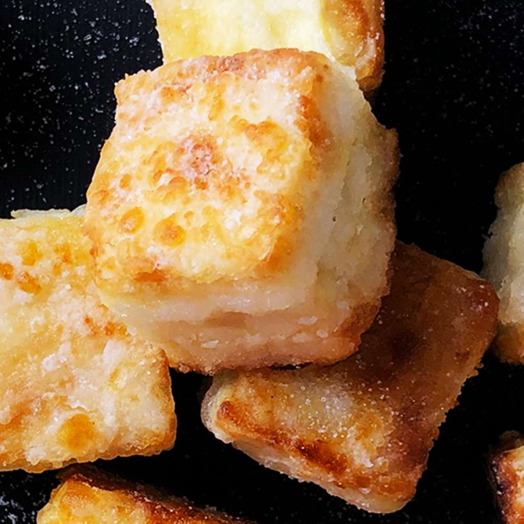 Close up of cubes of Salty Crispy Tofu, sprinkled with salt, all against a black background