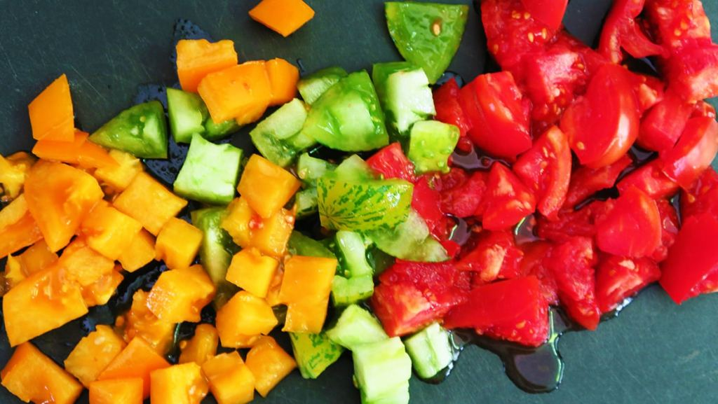 Topdown view of colorful tomatoes, chopped on chopping board. Chopping tomatoes is the third step for making Tomato and Bread Salad.