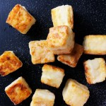 Cubes of Salty Crispy Tofu, sprinkled with salt, all against a black background