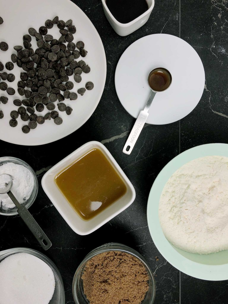 Topdown view of ingredients for making vegan brown butter chocolate chip cookies. Ingredients are chocolate chip cookies, aquafaba, vanilla, vegan brown butter, cornstarch, baking soda, flour, brown sugar and white sugar.