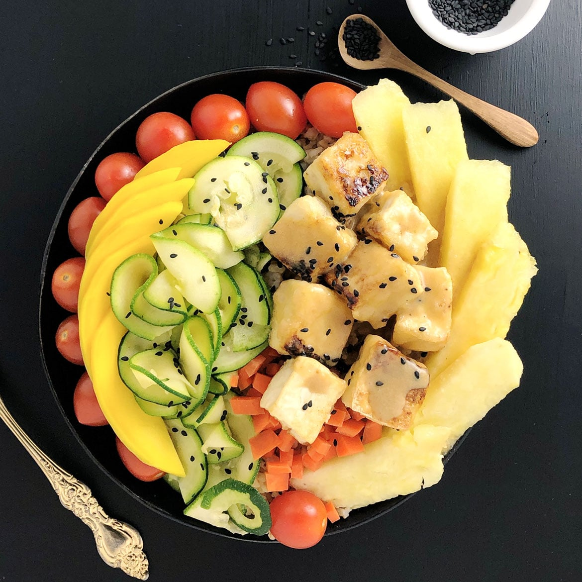 Top down view of Buddha Bowl with cherry tomatoes, mango slices, zucchini spirals, carrots, Salty Crispy Tofu topped with Pineapple Brown Butter Teriyaki Sauce, and fresh pineapple.