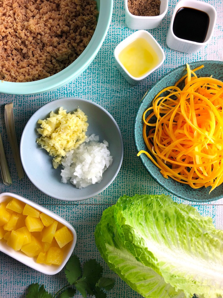 Image showing top-down view of ingredients for vegan version of lettuce wraps. In order from top left: TVP, brown sugar, soy sauce, pineapple juice, raw spirals of butternut squash, romaine lettuce, cilantro, pineapple, diced onion, diced ginger, and lemongrass.